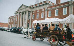 A covered wagon tour passes by the historic Truman Courthouse in Independence, MO.