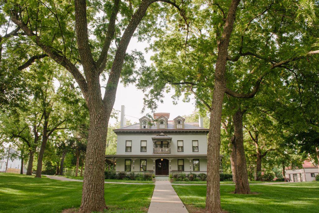 The Bingham-Waggoner Estate sites below the shade of trees in Independence, MO