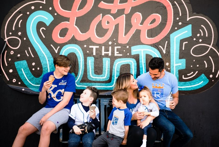 A family wearing KC Royals shirts and eating ice cream in front of a mural near the Independence Square in Independence, MO
