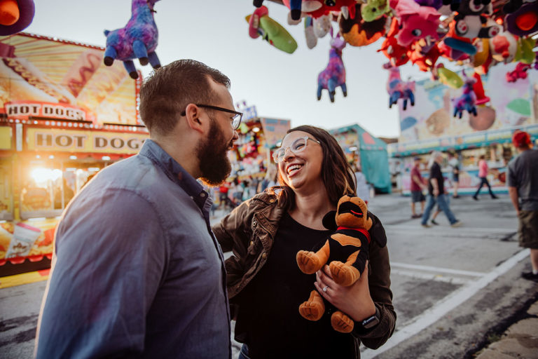 A couple smiles at each other after winning a stuffed animal from a carnival game at the SantaCaliGon Days Festival in Independence, MO
