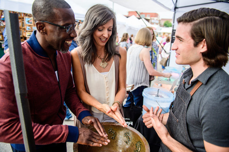 A couple interacts with a vendor at the SantaCaliGon Days Festival in Independence, MO