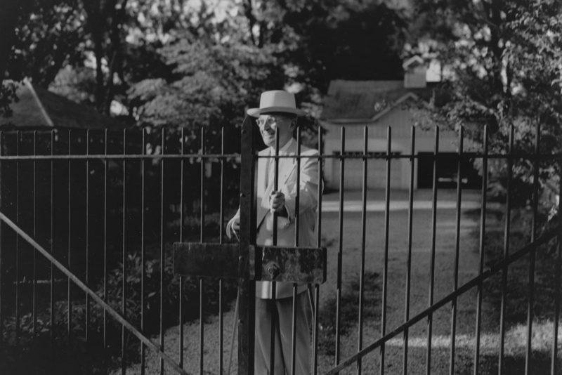 Harry S. Truman opens the gate at his home to begin his morning walk