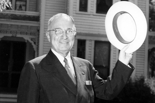 President Harry S. Truman stands outside his home in Independence, MO. He waves a hat toward onlookers.
