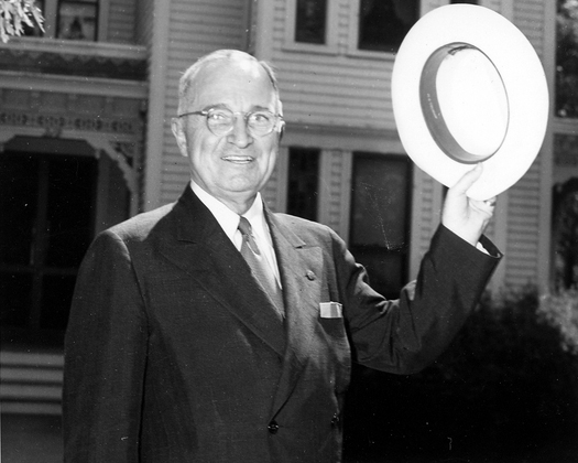 President Harry S. Truman waves his hat toward onlookers outside his home.