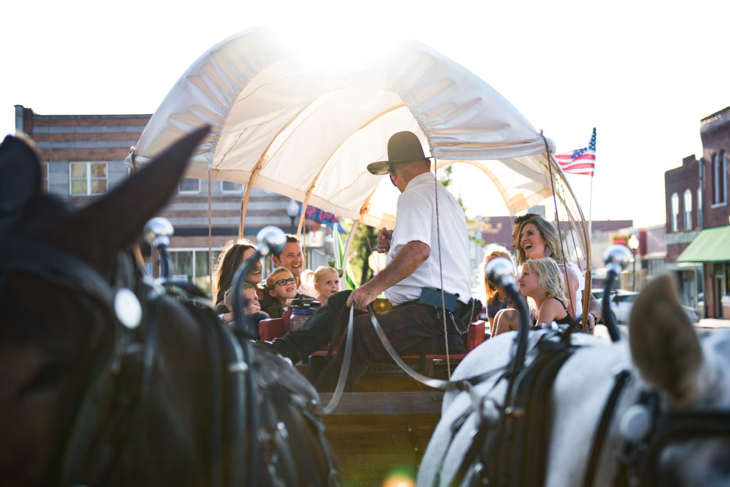 A mule-drawn, covered wagon carrying visitors on a tour of Independence, MO