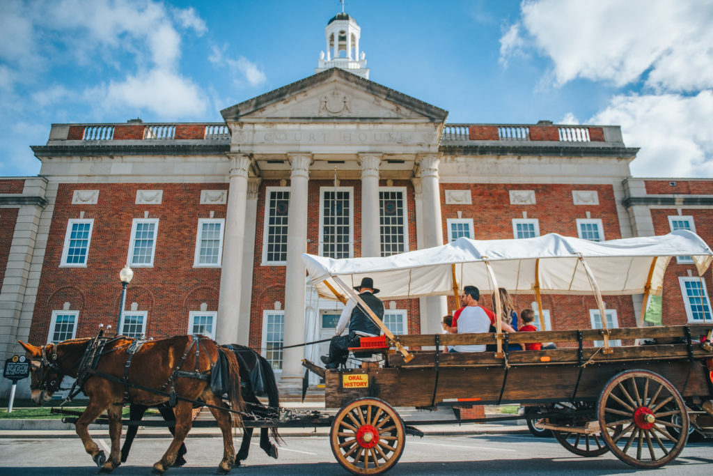 A covered, mule-drawn wagon passes by the Historic Truman Courthouse on the Independence, MO, Square