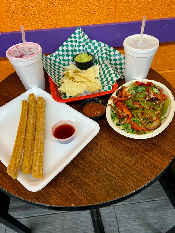 Burrito bowl, chips, and churros on a table at Paleteria El Chavo in Independence, MO