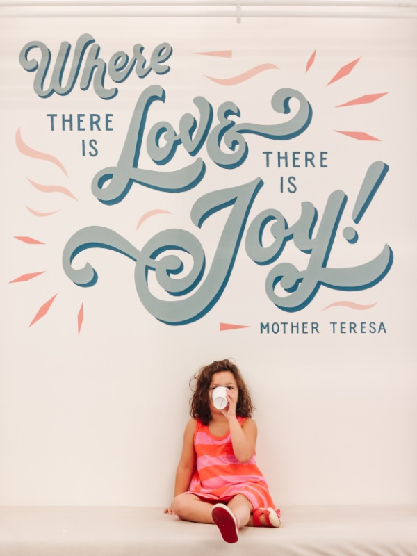 """Hattie Cowan sits below a """"Where there is love there is joy!"""" mural in Independence, MO"""