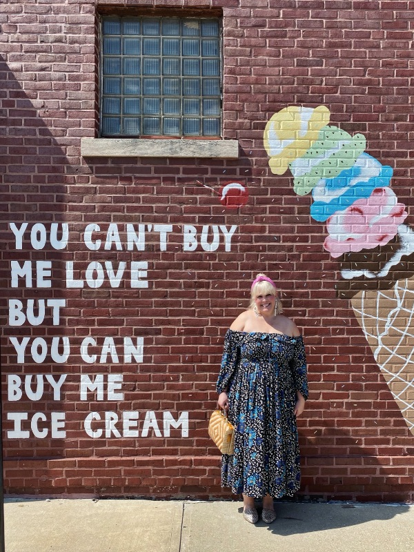 """Ann poses in front of the """"You can't buy me love but you can buy me ice cream"""" mural outside of Clinton's Soda Fountain in Independence, MO"""
