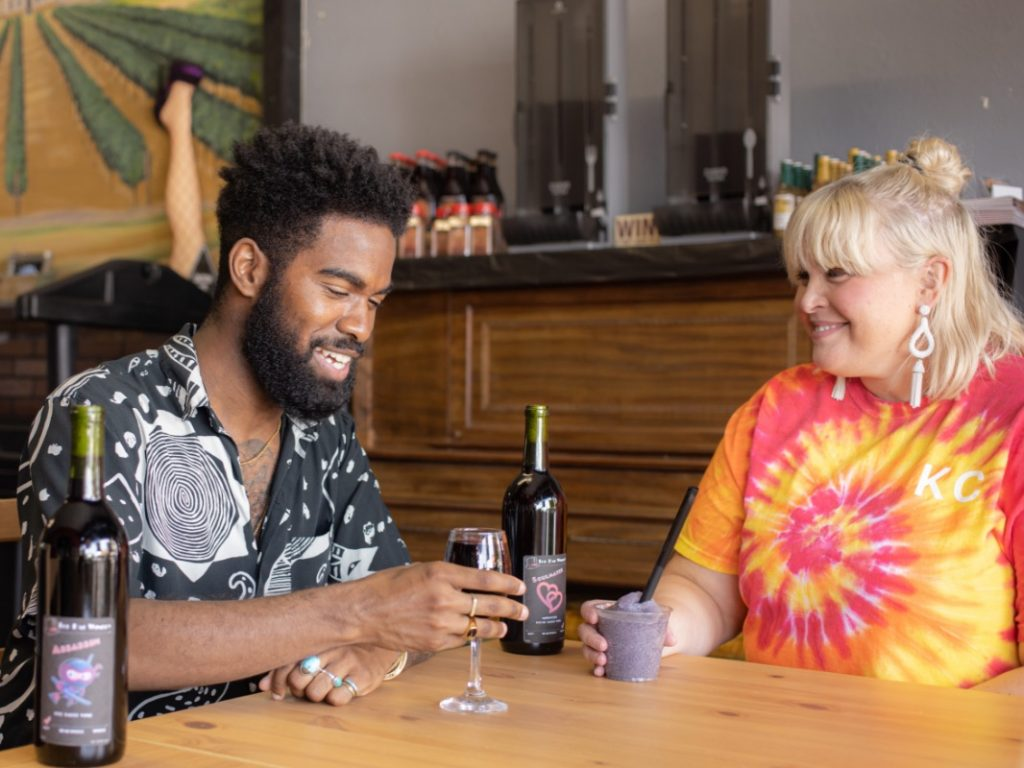 Influencer Jon Marzette and his girlfriend, Ann, hold drinks in Top Hat Winery in Independence, MO