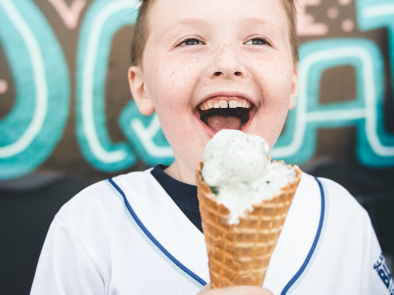 Boy smiles while eating an ice cream cone in Independence, MO
