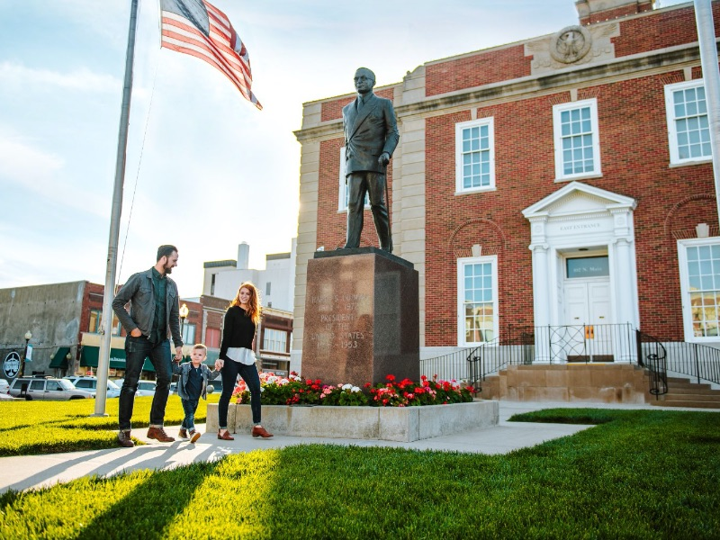 A family walks in front a statue of former President Harry S. Truman in Independence, MO