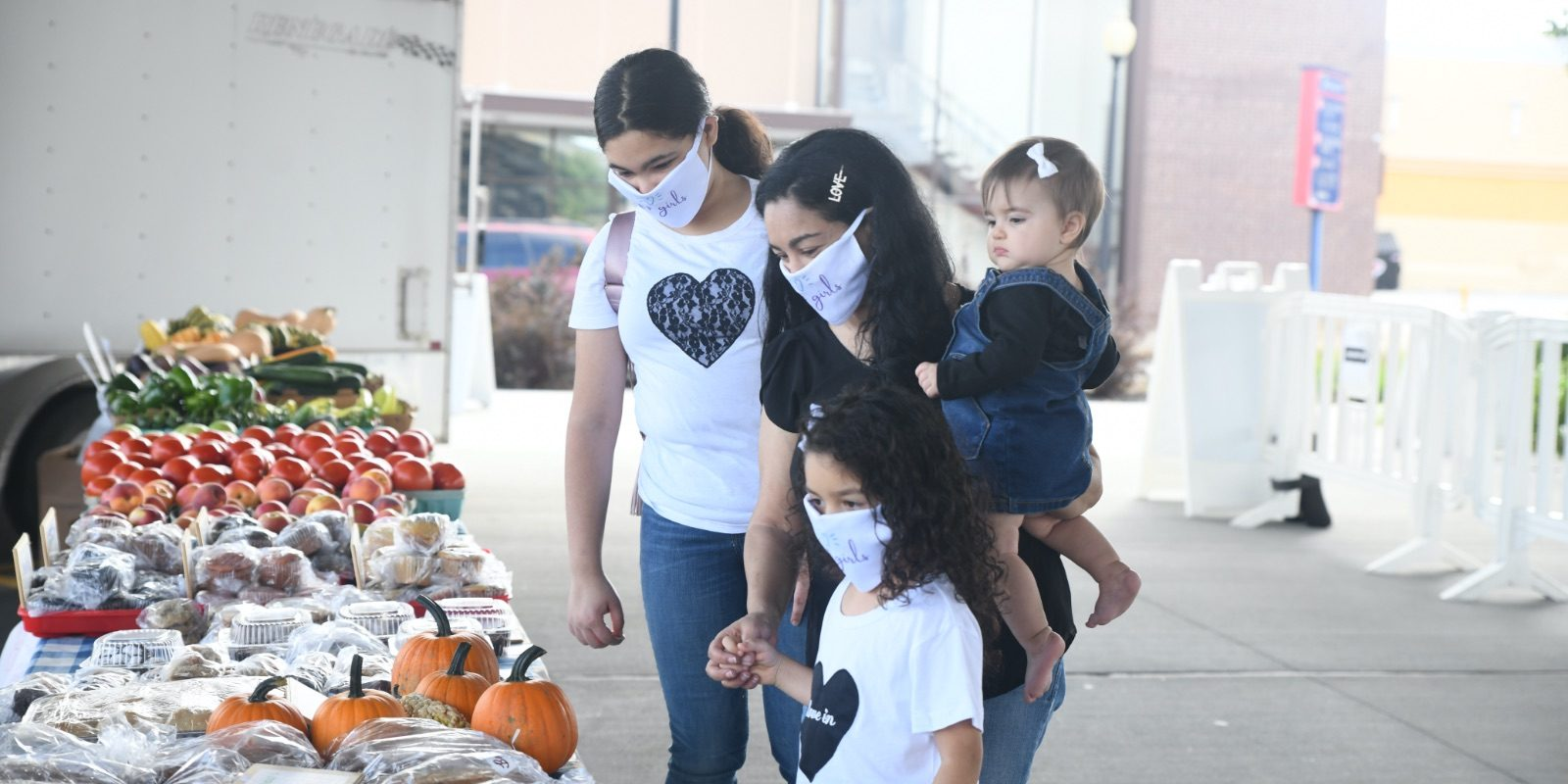 Elayna Fernández and her daughters browse the Uptown Farmers Market in Independence, MO