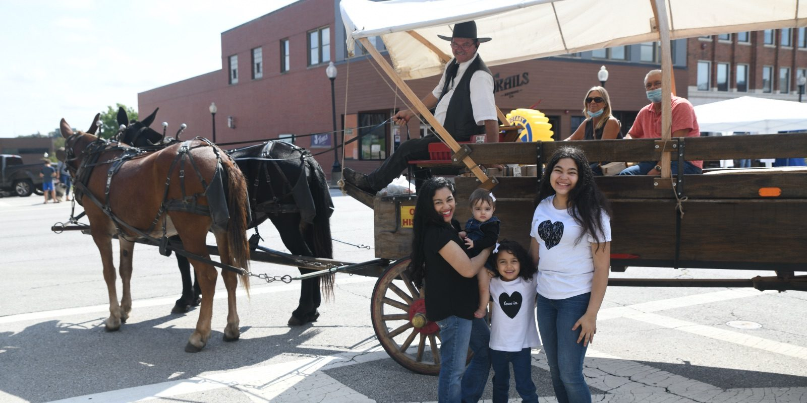 Elayna Fernández and her daughters pose in front of a Pioneer Trails Adventures wagon in Independence, MO